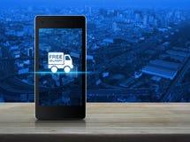 Icono libre del camión de reparto en la pantalla elegante moderna del teléfono en de madera foto de archivo libre de regalías