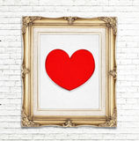 Icono rojo del corazón en marco de oro de la foto del vintage en la pared de ladrillo blanca foto de archivo