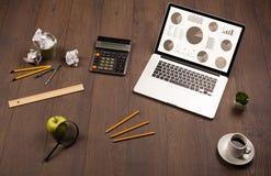 Iconos del gráfico del gráfico de sectores en la pantalla del ordenador portátil con los accesorios de la oficina Imagen de archivo libre de regalías