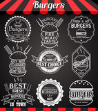 Iconos, etiquetas, muestras, símbolos e insignias determinados de la hamburguesa del blanco en la pizarra Imagen de archivo