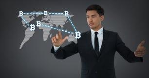 Iconos gráficos del bitcoin conmovedor del hombre de negocios en mapa del mundo Fotografía de archivo libre de regalías