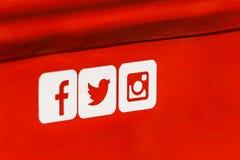 Iconos sociales de Facebook, de Twitter y de Instagram medios en fondo rojo del metal Imagen de archivo libre de regalías