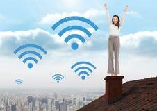 Iconos y empresaria de Wi-Fi que se colocan en el tejado con la chimenea y la ciudad Foto de archivo
