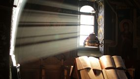 Icons of the Christian Church. In the background of the light from the window and holy books closeup stock video