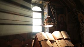 Icons of the Christian Church. In the background of the light from the window and holy books closeup stock video footage
