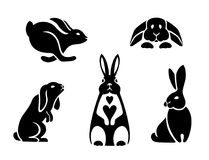 Silhouettes of hares in different poses, the logo of a rabbit. Icons rabbits, logo hare sitting, running, jumping, standing on hind legs, snuggled to the floor Royalty Free Stock Photos