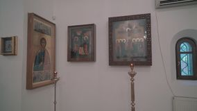 Icons on the wall in the Orthodox Church and candles are nearby. Panorama. The camera is in motion stock video footage