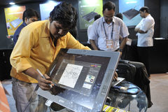 ICT  Fair in Kolkata. KOLKATA- FEBRUARY 20: A visitor draws on a screen with a cordless touch pen during the Information and Communication Technology (ICT) Stock Photography