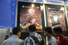 ICT  Fair in Kolkata. KOLKATA- FEBRUARY 20: Young adults checking a HP DreamScreen , during the Information and Communication Technology (ICT) conference and Royalty Free Stock Photo