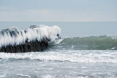 Icy breakwater in the winter sea stock photo