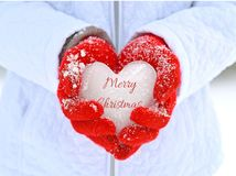 Icy Christmas heart in red gloves Stock Photo