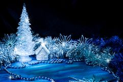 Icy Christmas tree glowing with silver light on a blue background. In the corner. Surrounded with little white house, silver tinsel and snowflakes. Light brush Stock Photo
