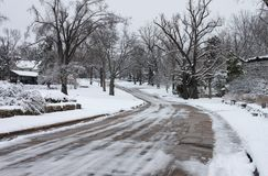 Icy city neighborhood street with snow covered houses and trees Stock Photos