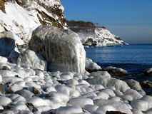 Icy coastline landscape. Landscape of a rocky ocean coastline covered in ice and snow on a clear day Royalty Free Stock Images