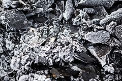Icy cold on black coals as background Stock Photo