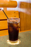 Icy Cold Drink. Clear glass with ice and cola-flavored drink sitting on coaster on table with black straw Royalty Free Stock Images