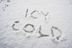 Icy cold written in white snow Stock Images