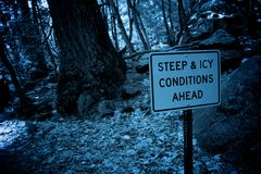 Icy Conditions ahead. A warning sign of steep and icy conditions ahead Stock Photo