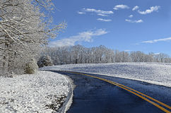 Icy Curving Road. Beautiful winter landscape showing a curve in an ice covered winter road surrounded by snow covered land royalty free stock photography