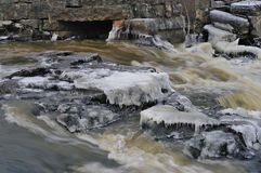 Icy frozen river on murky winter day. Small stream, grass and stones covered with ice royalty free stock photos