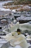 Icy frozen river on murky winter day. Small stream, grass and stones covered with ice stock photography