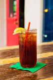 Icy Glass of Ice Tea with a Red Straw and Lemon at an Outdoor Cafe. Close-up shot of an icy glass of tea with lemon and a red straw on a bright green napkin at Stock Photography