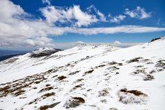 Icy hillside on a blue day. Landscape from a snowy mountain in winter wit a blue sky royalty free stock image
