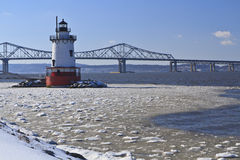 Icy Hudson and Lighthouse. Sleepy Hollow lighthouse in front of the Tappan Zee Bridge on an icy Hudson River in New York Royalty Free Stock Image