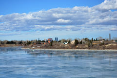Icy lake view of park and city. Icy lake view with historic park and city in the distance. Late winter with ice melting on lake with reflection Stock Photo