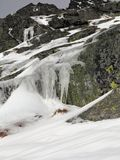 Icy Mountain Rocks. Rocks Covered With Green Coating. Icicles Hanging From the Rocks. royalty free stock photos