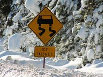 Icy patches road warning sign on ice and deep snow Royalty Free Stock Photos