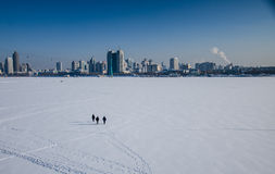He icy river. Three pedestrian walk far away from the icy river songhua river in Harbin city Stock Images