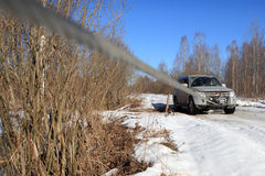 Icy road in  woods, rope extends from winch stuck car. Stock Image