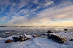 Icy sea and colorful sky. Photo is taken from icy beach in Helsinki, Finland Stock Photo