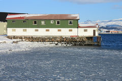 Icy sea & factory. Small fish factory on the Fjord of Busknes, Lofoten islands, frozen in wintertime royalty free stock image
