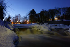 Icy and snow covered rapids in a wintery evening a Stock Image