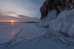 The icy splashes on the rock at dawn light. Winter lake Baikal, cape Oltrec Stock Image