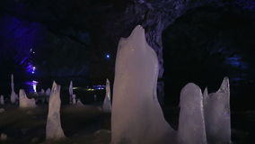 An icy stalagmite on the undeground lake in the big marble cave stock video