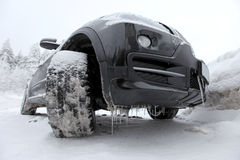 Icy SUV Car. Icy SUV wheels and underbody in a snowy landscape - very low camera angle for an impressive look Stock Photo