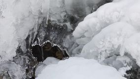 Icy Trickle Loop. Water flows beneath ice and snow in this seamless loop stock footage