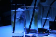 Icy Water Glasses. Cold glasses of water and ice on a blue-lit bar, next to an ashtray and other drinks Royalty Free Stock Photos
