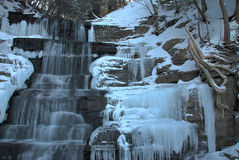 Icy Waterfall. Icicles form all around a winter waterfall. Despite the cold the water still flows down over the rock steps as the afternoon sun is just visible Stock Images