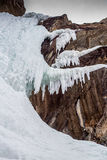 Icy waterfall at rock cliff in winter time Stock Images