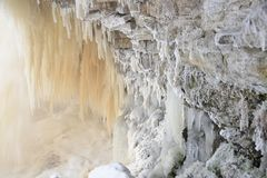 Icy waterfall scape. Frozen Jagala river waterfall long exposure. Rocks covered by ice and snow, long stalactites of ice Stock Photos