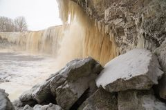 Icy waterfall scape. Frozen Jagala river waterfall long exposure. Rocks covered by ice and snow, long stalactites of ice Royalty Free Stock Photo