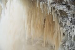 Icy waterfall scape. Frozen Jagala river waterfall long exposure. Rocks covered by ice and snow, long stalactites of ice Stock Photo