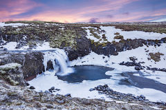 An icy waterfall during sunrise in Iceland Stock Image