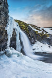 An icy waterfall during sunrise in Iceland. A cold snowy waterfall in the highlands of Iceland framed by pastel skies and rugged terrain offers scenic landscape Royalty Free Stock Photos