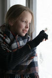 Icy window. A girl looking through icy window Stock Images