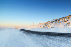 Icy winter road deicing sprinkled with black sand. Royalty Free Stock Images
